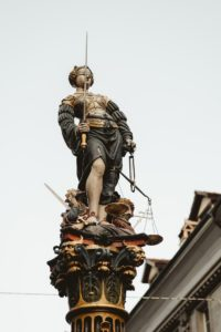 Statue holding scales of justice in one hand and sword in the other - full color statue with gold armor and sword