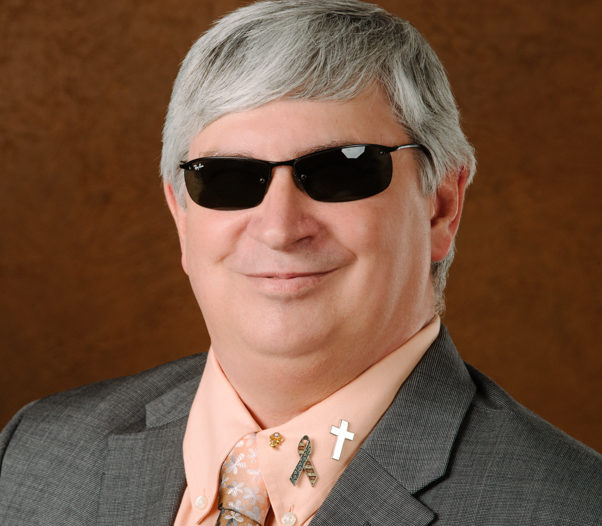 Doug Towne Founder and CEO , smiling in a peach shirt and tie, wearing a gray blazer