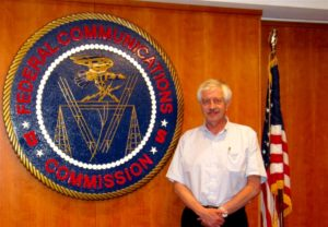 Dr. Paul Michaelis standing between the United States flag and Federal Communications Commission emblem