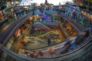 This colorful time lapse image of the interior of a shopping mall shows many people.