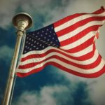 American Flag with blue sky and white clouds. We believe everyone should be able to access information technology.
