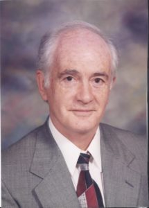 Rev Dr. Martin G. Lewis pictured in a gray suit with a similar background
